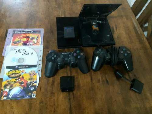 Play station 2 con sus accesorios y un control inalámbrico.