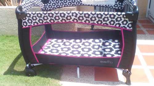 Corral y coche para bebés gris con negro y rosado.
