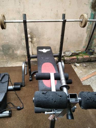 Banco de pesas con ejercitador de piernas y brazos rematando